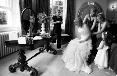 The bride gets help from her bridesmaides
