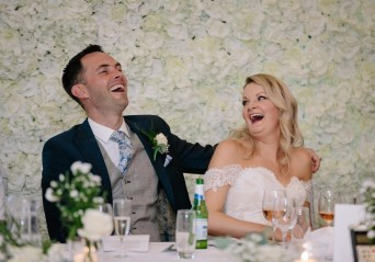 The bride and grrom laugh during the speeches
