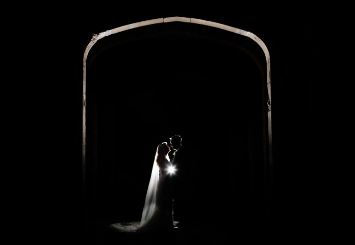 Bride and Groom beneath the arch at The Mere Wedding