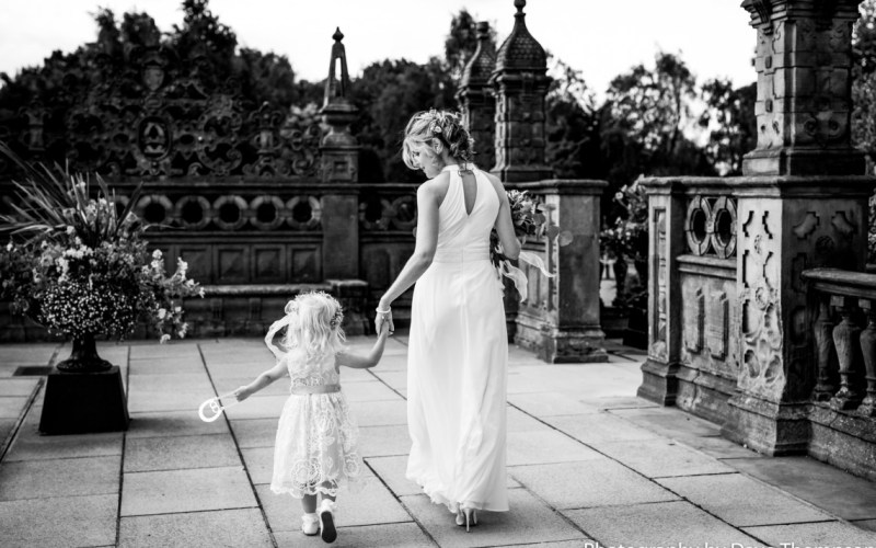 Bride hand in hand with her daughter at Crewe Hall