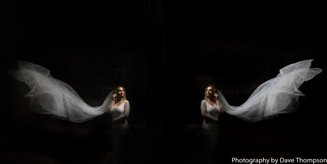 A bride and her veil reflected in glass