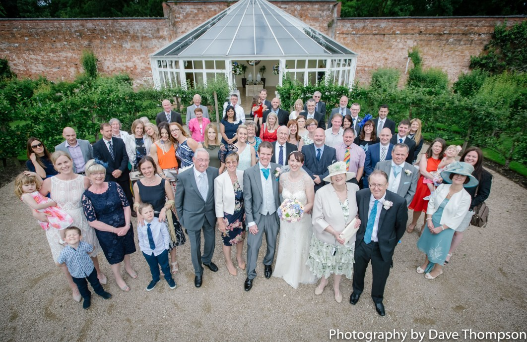 All the wedding guests gather for a photograph outside the glass house.