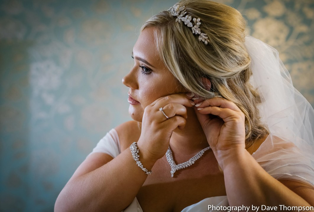 The bride puts her earrings in at Heaton House Farm