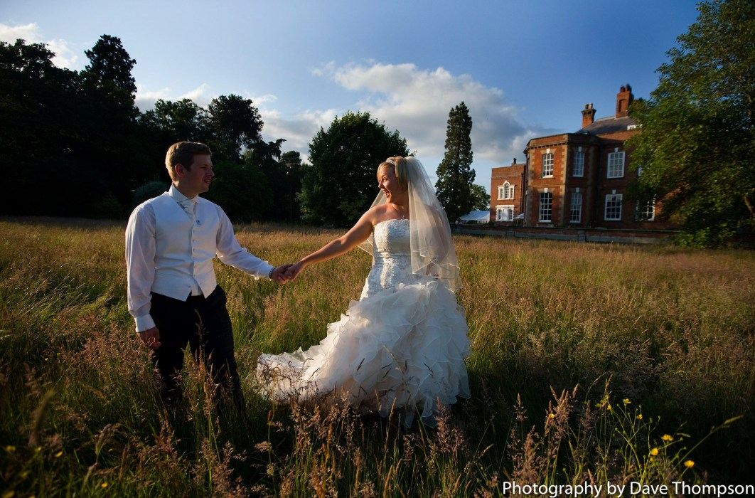 Newlyweds walking through the gras in front of the Country House at Iscoyd Park, Shropshire.
