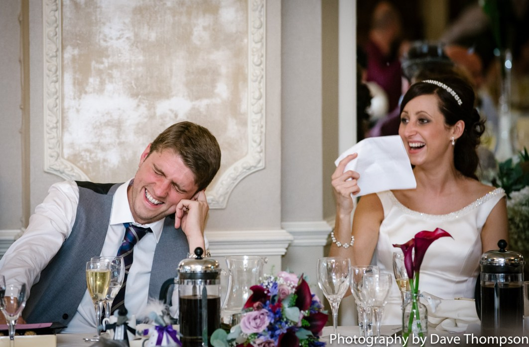 The bride and groom laugh during the best mans speech.