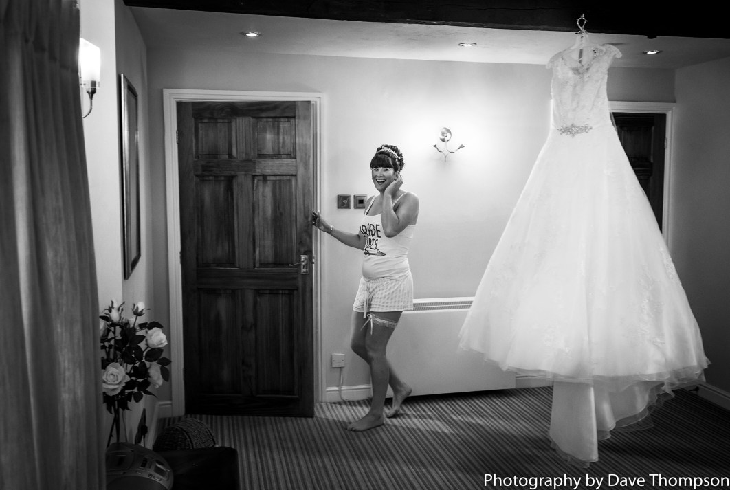 The bride in her casual clothes alongside her dress as it hangs from a beam