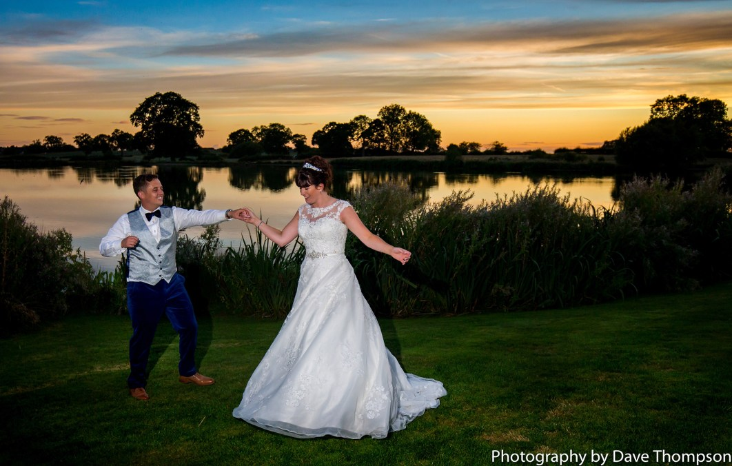 Bride and groom dancing alongside the lake