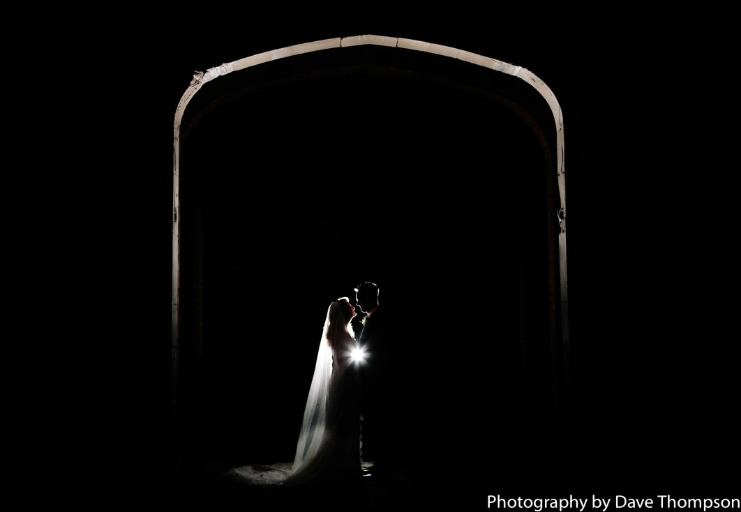 Off camera flash portrait of the bride and groom under the Mere Arch