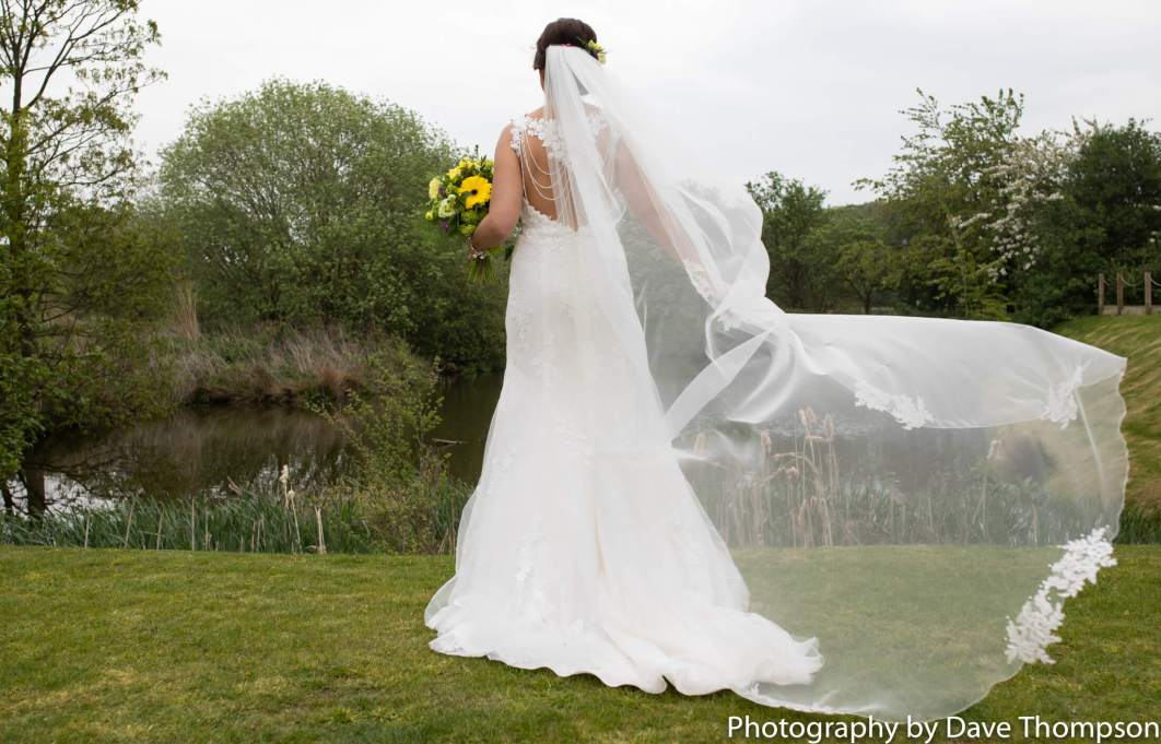 A bride stands next to the lake