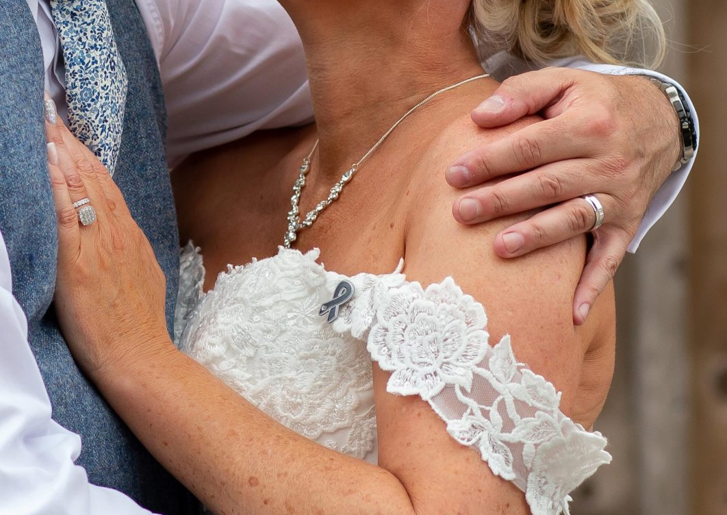 The bride wearing a Christies Cancer charity badge