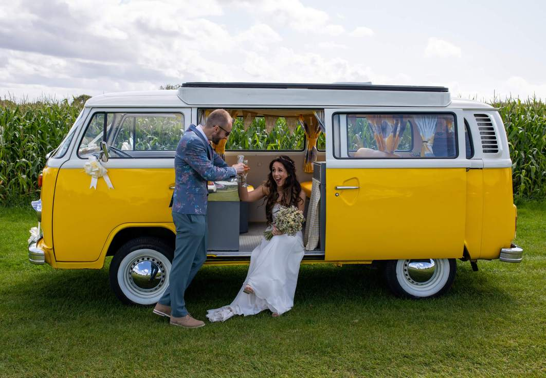 A bride and groom have a drink sat in a yellow VW camper van