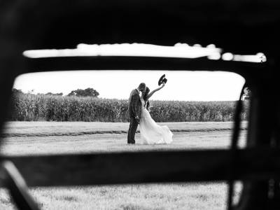 A black and white image as the bride removes a cowboy hat.
