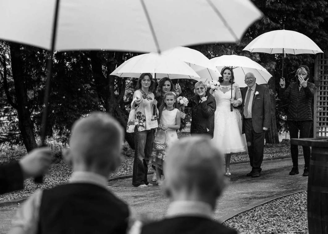 The bride, her father and bridal party arrive beneath umbrellas at Alcumlow Wedding Barn in Cheshire.