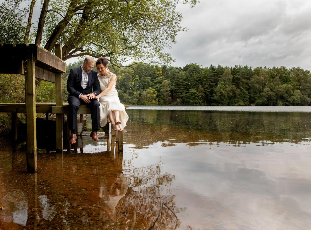 A bride and groom relax by the lake at Nunsmere Hall in Cheshire
