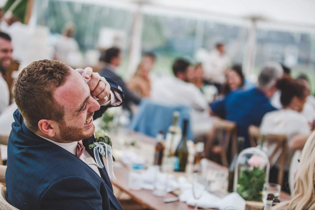 A groom laughs during the speeches at a marquee wedding