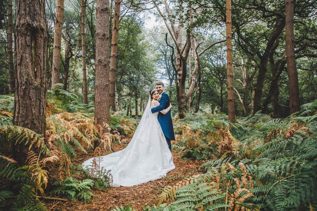 The bride and groom in the woods at Peckforton Castle