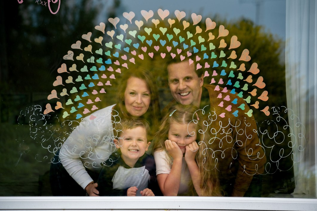 A family pose for a photograph inside their lounge behind a rainbow painted on the glass.