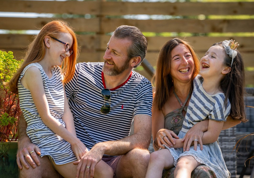 A husband and wife laugh with their two daughters during a family doorstep photograph