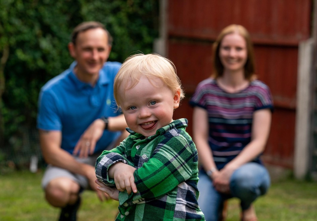 A toddler poses with in front of his mum and dad.