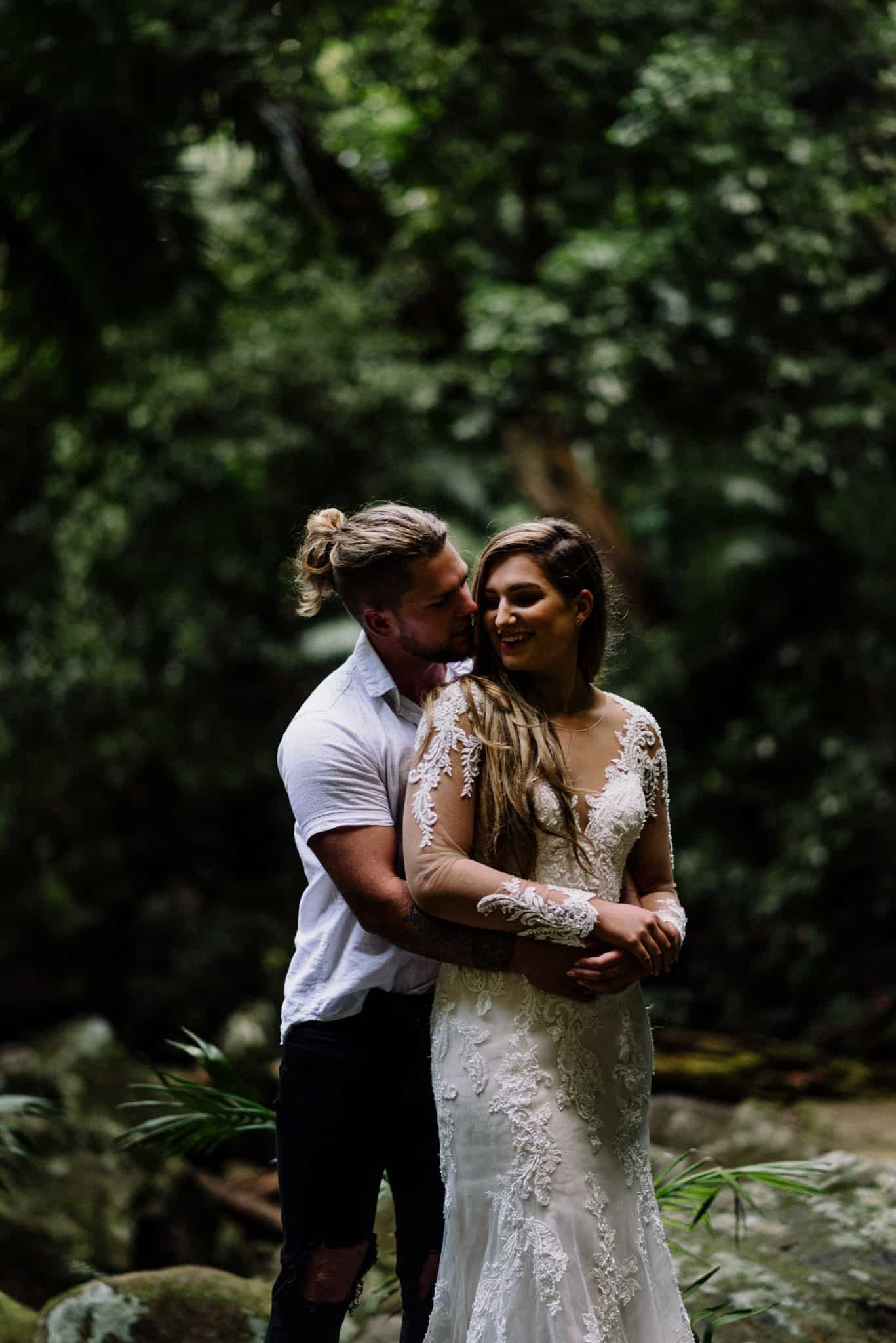 Bride and groom share a cute hug during their forest elopement down by a waterfall