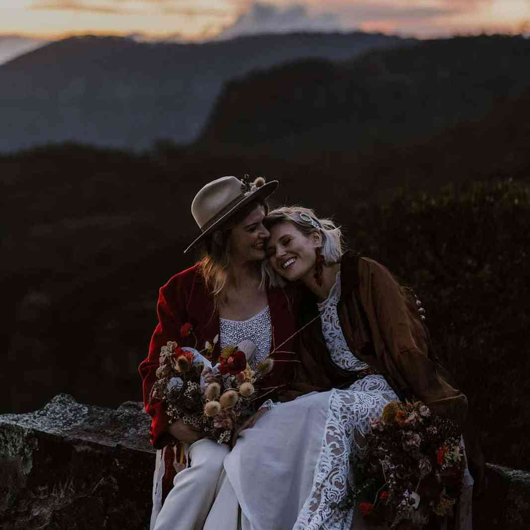 Gorgeous brides sit on mountainside at sunset after eloping NSW