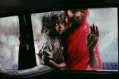 """INDIA-10214, Bombay, India Mother and Child at Car Window, Bombay/Mumbai, India, 1993 A mother and child beg for alms through a taxi window during the monsoon. Bombay is the capital of India's business, movie, music, and fashion worlds. A city of wealth, but everywhere, within a few steps, is the greater India. Poverty, for both its victims and those who only witness it, is inescapable. Refugees from India's rural poverty and people seeking opportunities for a better life arrive each day in the thousands to swell a city which already seems to burst at the seams. Over time, you learn of the complex economics of Bombay's beggars. Street corners can be """"inherited"""" or subject to leasing arrangements; a spot on one intersection busy with taxis is prime real estate. Begging is a way of life. An overwhelming number of the city's inhabitants live on the streets in intricate hierarchies-those that have shelter are better off than those on open ground. They in turn have risen above those who live on the streets themselves. (2000) South SouthEast. London: Phaidon Press Limited, 43. National Geographic, March 1995, Bombay: India's Capital of Hope Magnum Photos, NYC5919, MCS1996002 K097 ..Phaidon, 55, South Southeast, Iconic Images, final book_iconic, final print_milan Jam-packed and alive with commerce, India's richest country allures new corners by the hundreds each day. Arriving with little more than dreams, some hit it big. Others remain on the outside looking in: half of Bombay's 13 million people live on the streets or in ramshackle huts, and thousands-like this woman and child-survive only by begging. National Geographic: John McCarry (March 1995) Bombay: India's Capital of Hope, National Geographic. (vol.187 (3)) pp.42-67 *See caption in book. Iconic Photographs"""
