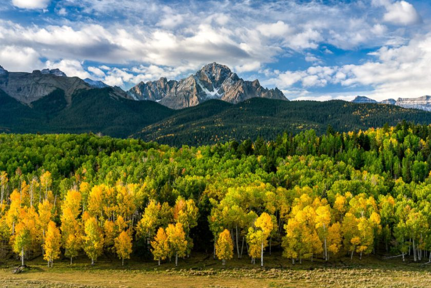 This landscape photo shows the San Juan Mountains in Colorado with fall colors in the aspen trees.