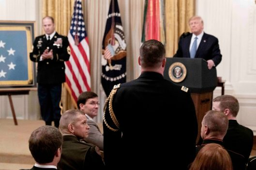 Lieutenant Colonel KYLE WALTON (back to camera) stands as President DONALD TRUMP (standing in back to right) commends members of the Army Green Berets team who worked with Army Master Sgt. MATTHEW WILLIAMS (standing in back to left), as Williams receives the Medal of Honor for heroism while serving in Afghanistan's Shok Valley in 2008. Oct. 30, 2019