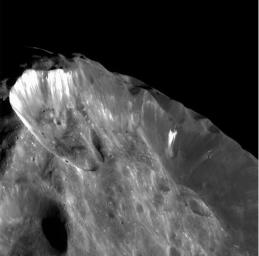 This image from NASA's Cassini spacecraft shows bright wispy streaks thought to be ice revealed by subsidence of crater walls.