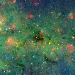 Astronomers have found cosmic clumps so dark, dense and dusty that they throw the deepest shadows ever recorded. A large cloud looms in the center of this image of the galactic plane from NASA's Spitzer Space Telescope.