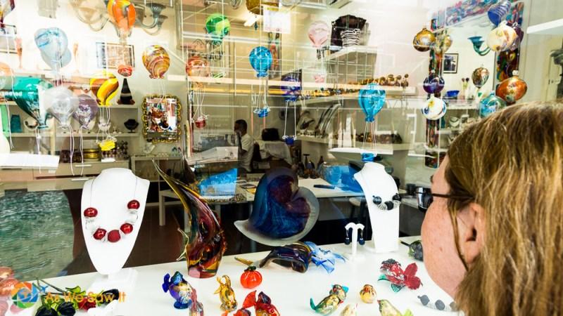 Linda looks in Murano glass shop window, glass blower in the shop