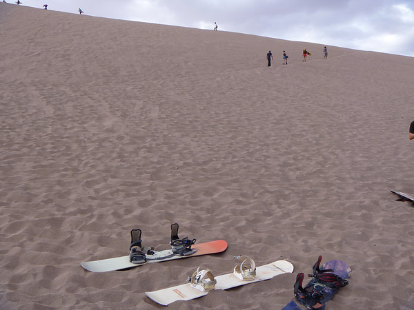 To sandboard, you just need a board and the will to hike up giant sand dunes.  Then strap yourself in and slide down!