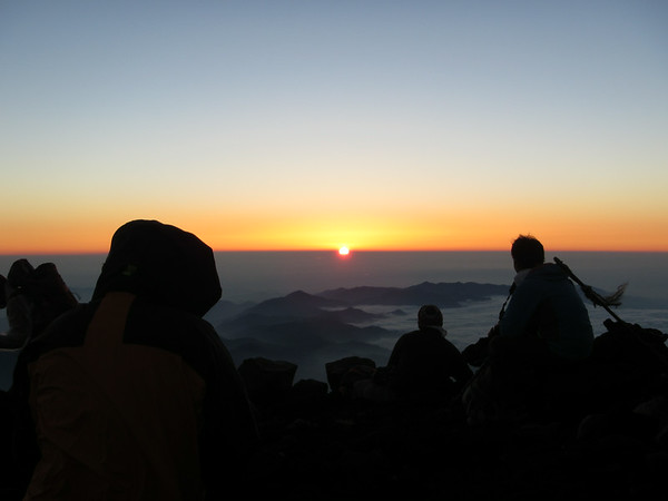 Enjoying the beautiful sunrise at the summit of Mt. Fuji.
