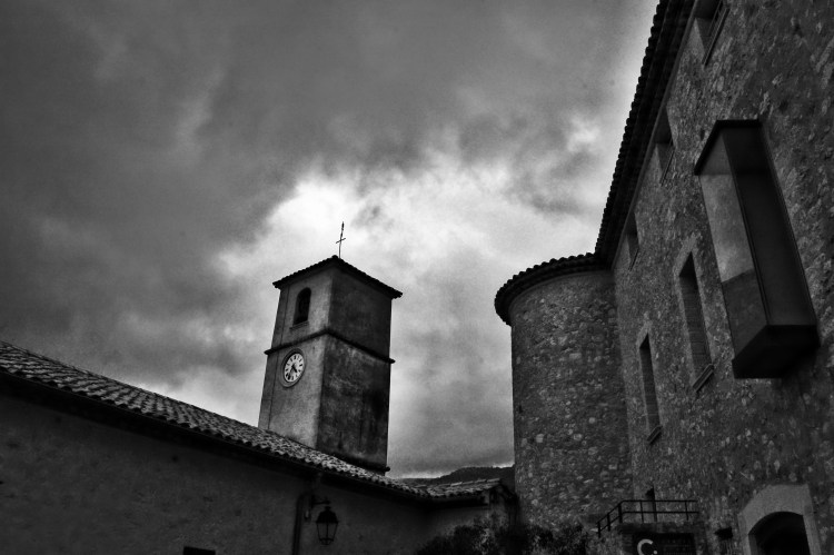 Un clocher d'église et un château en pierres, sous des nuages noirs