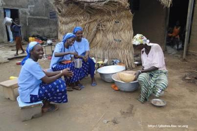 Visite, avec les novices, d'une dame qui prépare la boisson locale