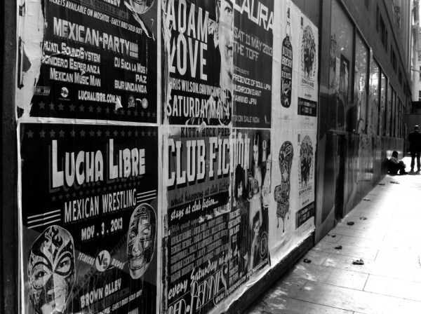 in black and white, posters on the side of a building
