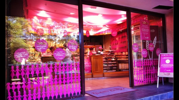Baker's Delight shopfront decorated with pink paper dolls and lights
