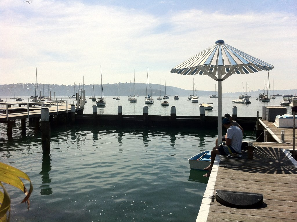 wharf with a wooden umbrella, overlooking sailing boats