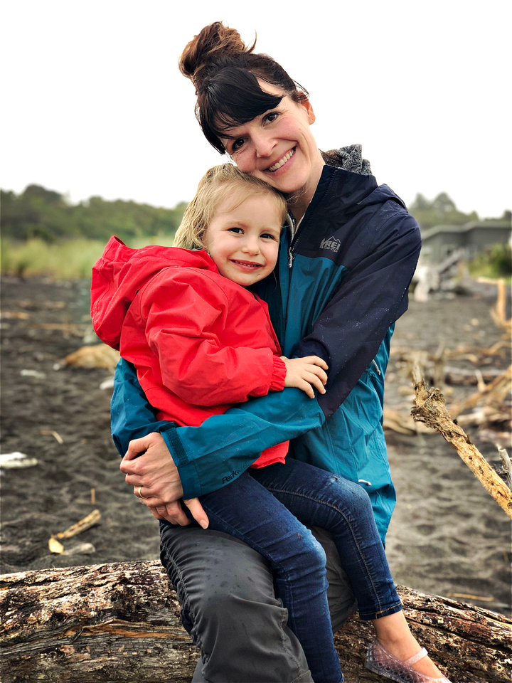 A woman and young girl sit on a log on New Zealand's West Coast, in Hokitika. They are wearing red and blue rain jackets, and the dark gray sand is wet from a fresh rain.
