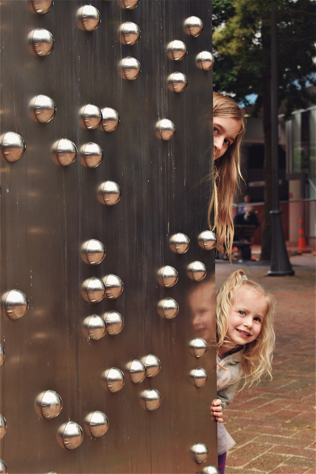 Two girls peek out from behind a large braille sculpture in downtown Wellington, New Zealand.