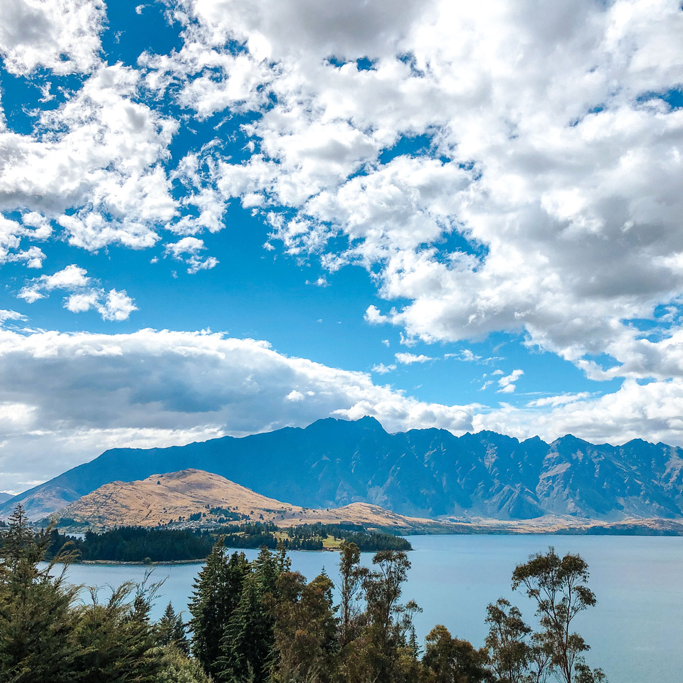 A morning view of Lake Wakatipu from the hills outside of Queenstown at sunset.  The Remarkables mountain range is visible across the lake, beyond the peninsula and Queenstown golf course.