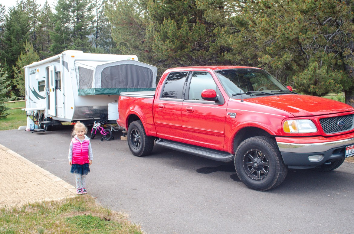 Best Camping in Idaho - Lake Cascade State Park.  A young girl stands in front of a 2001 Ford F-150 Lariat pulling a hybrid Starcraft travel trailer with a pop-out canvas sleeping area.  The photo depicts a campsite at Idaho's Cascade Lake State Park near Tamarack Resort and Donnelly, Idaho.