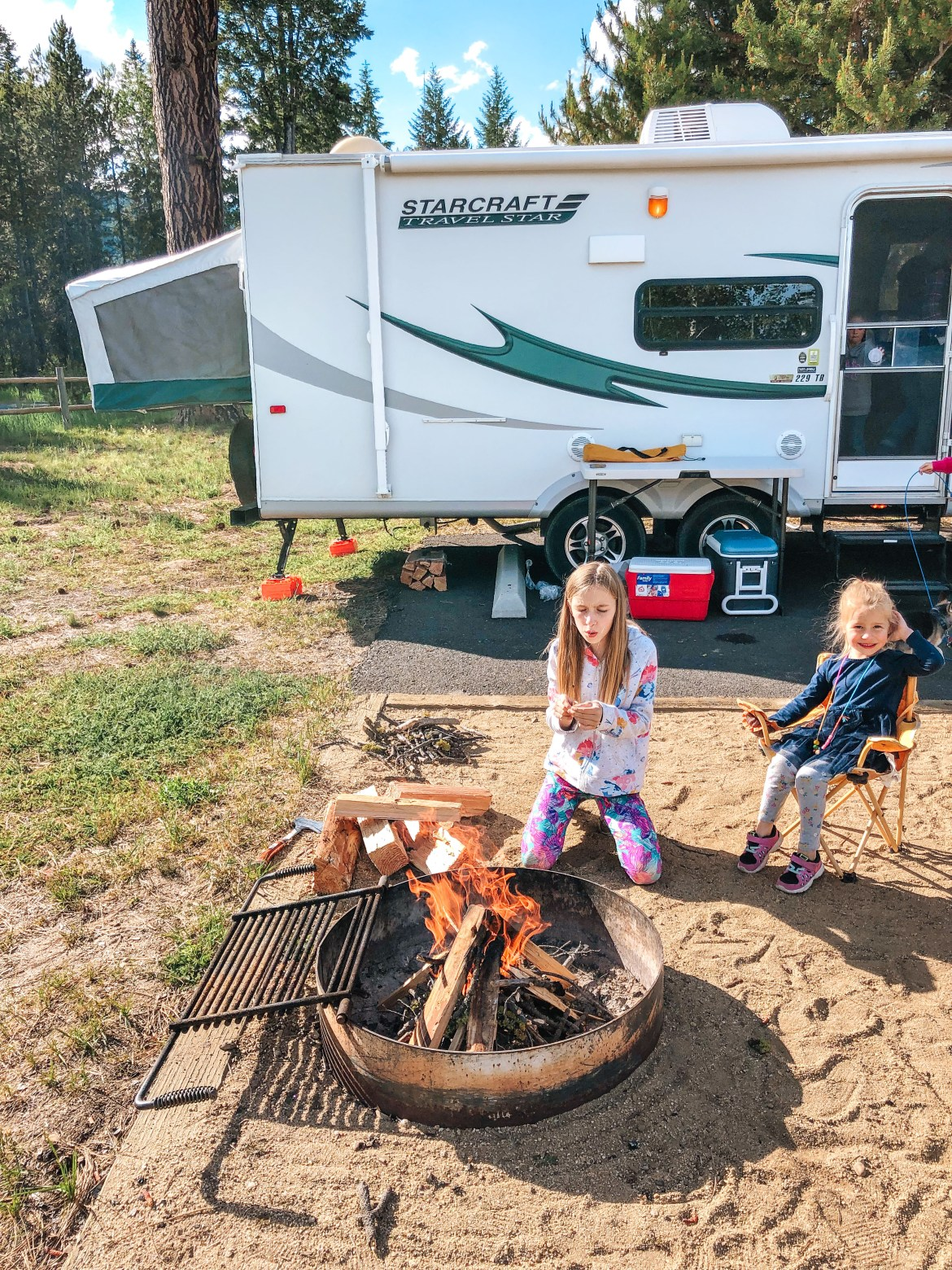 Two young sisters sit in camp chairs around a fire pit and fire at a campsite at Idaho's Cascade Lake State Park near Tamarack Resort and Donnelly, Idaho. Two coolers are visible near a table and stacked wood nearby a hybrid 2012 Starcraft travel trailer.  One of the trailer's canvas pop-out beds is visible in the background.