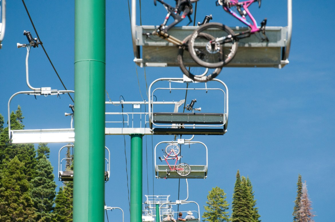 Idaho Resorts: Tamarack Resort.  Riding the ski chair lift in summer at Idaho's Tamarack Resort near Donnelly and Cascade off of Highway 55.  Mountain bikes hang off the back of empty chairs as they ascend the mountain lift.  The resort operates the ski lift throughout the summer for mountain biking, hiking, and the resort's zip line through the forest.