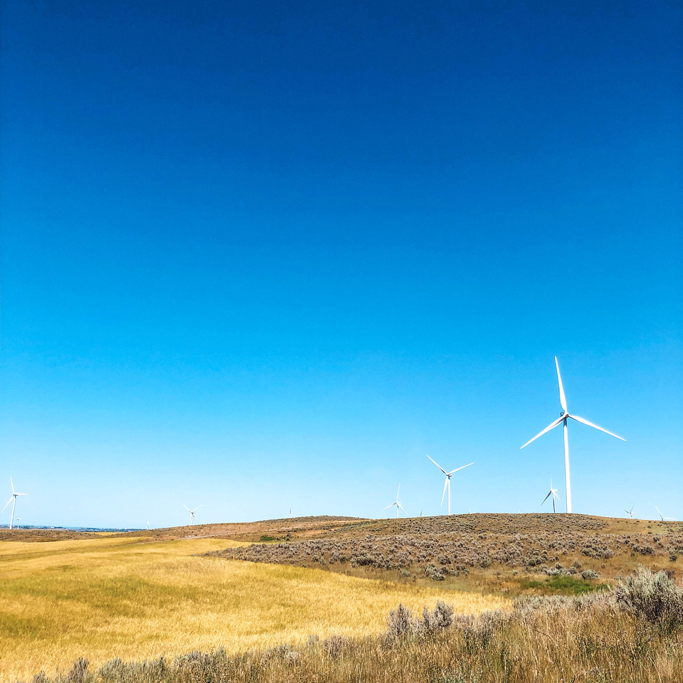 Giant wind turbines sit in rural farmland near Massacre Rocks State Park and American Falls, Idaho.  Vibrant blue skies contrast with the long, white arms of the turbines as they spin in the wind in Eastern Idaho.