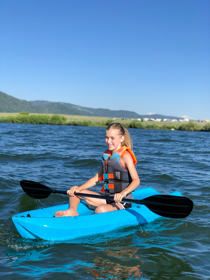 A young girl sits in her hardshell youth kayak and floats on the lake at Idaho's Henrys Lake State Park.  The park, just 15 miles from the West Gate to Yellowstone National Park, is known for native cutthroat trout, world-class fishing, and gale-force winds.