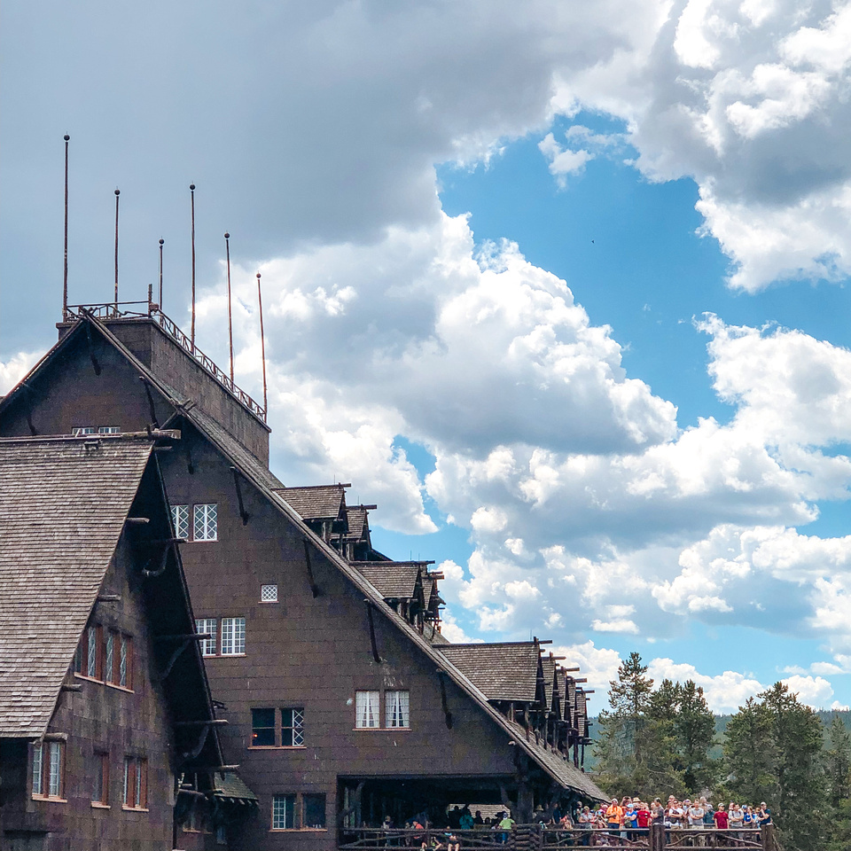 Yellowstone Vacation: The second-story viewing platform at the Old Faithful Inn in Yellowstone National Park, Wyoming, looks out to Old Faithful below.  Tourists gather on the platform of the Inn to watch Old Faithful erupt.