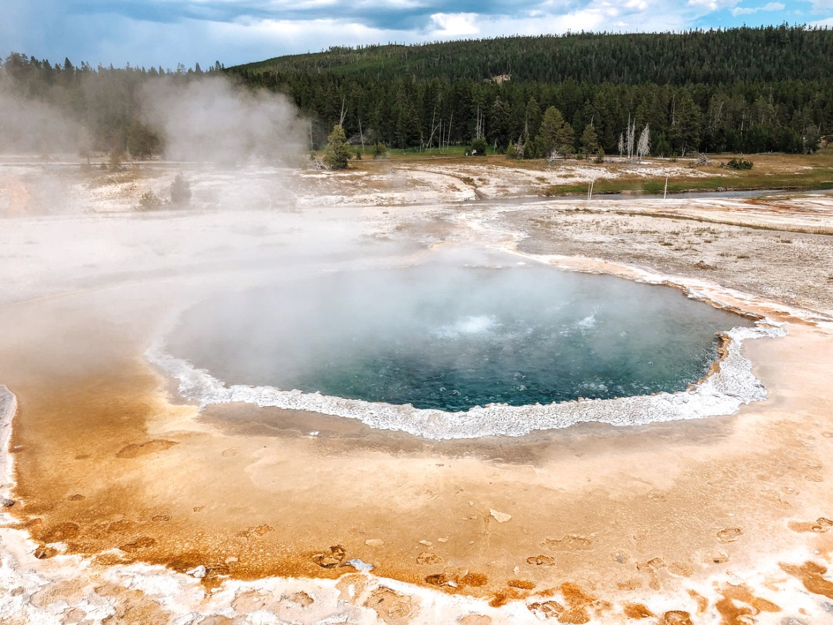Bacteria mats and hot springs at the Upper Geyser Basin in Yellowstone National Park, Wyoming.  Hot water from thermal pools above the Firehole River trickles down into the river, leaving streaks of color along the ridge and riverbank.