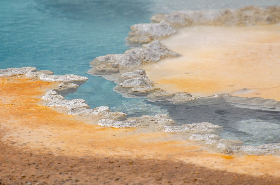 A large, multicolored thermal spring near Old Faithful Geyser and the Upper Geyser Basin in Yellowstone National Park, Wyoming.  Deep blue water contrasts with the orange, brown, and gray mineral earth and bacteria mats surrounding the spring.