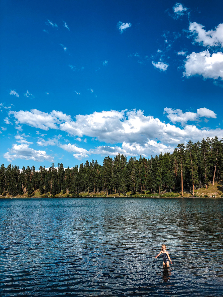 A young girl stands in shallow water near the sandy beach at Oregon's Magone Lake, near John Day, Oregon.
